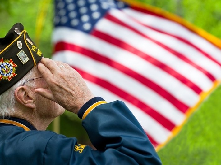 Older adult male veteran salutes the American flag.
