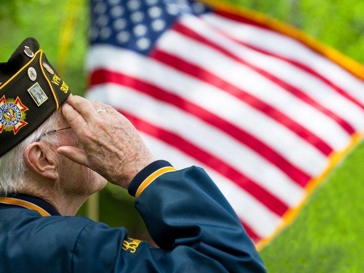 Older adult male veteran salutes the American flag.